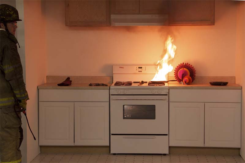 A pan is on fire on a stovetop. Click next to see what happens when you try to put the fire out with water.