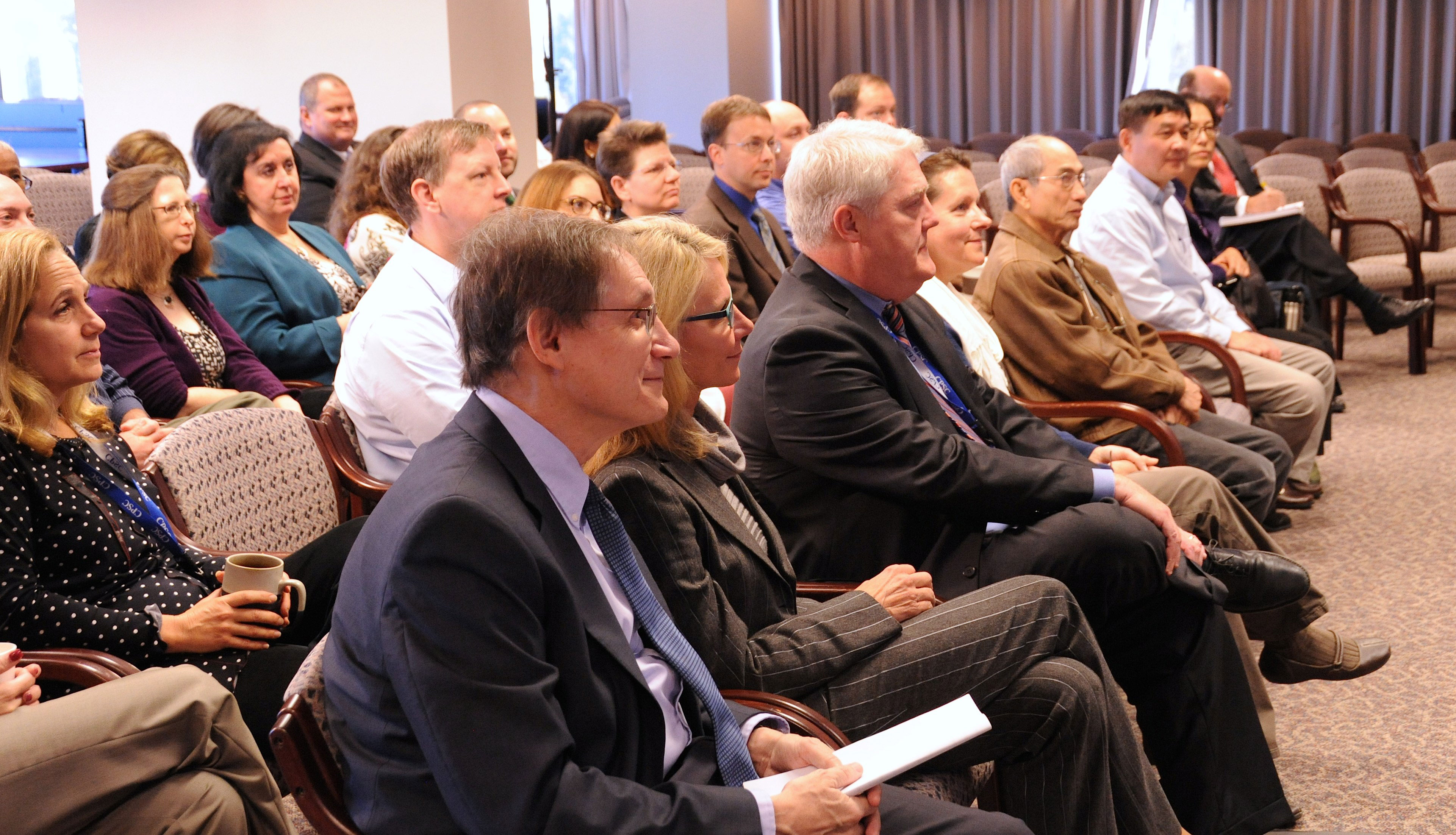 Commissioner Adler, Commissioner Robinson and other members of the audience listen to the winners present their apps.