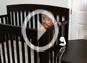 Imagen con botón de reproducción de bebé en una cuna alcanzando un cable de monitor