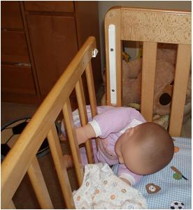 Picture of recalled crib with baby trapped