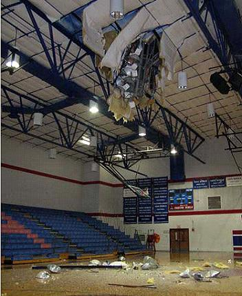 Picture of light pole fallen through gymnasium roof