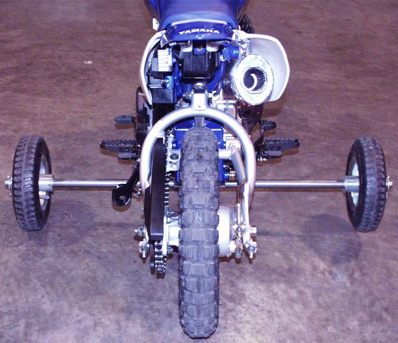 The training wheels attach to the underside of the motorcycle frame beneath the engine.