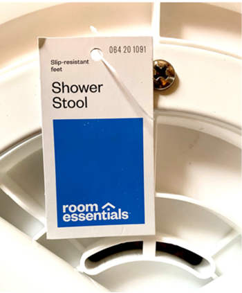 The Room Essentials logo and item number 064-20-1091 are printed on the front of the recalled shower stool's hangtag.