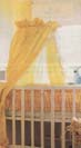 Yellow canopy attached to a stand which is clamped to the frame of a crib.