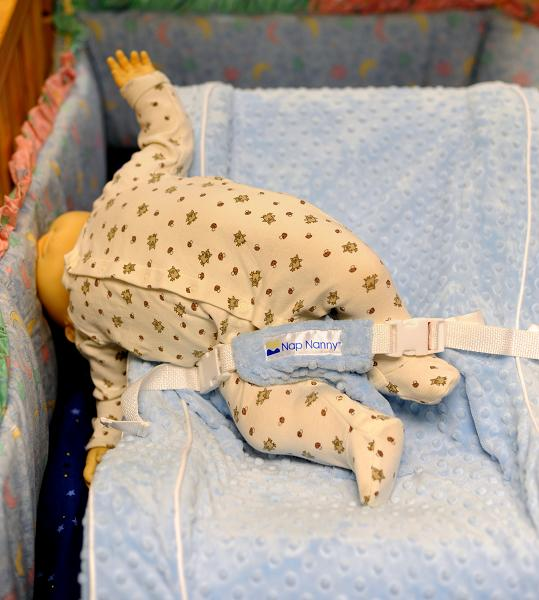 Doll falling over side of recliner placed inside a crib