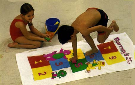 Kids playing Hopscotch  on a Barney Game Towel